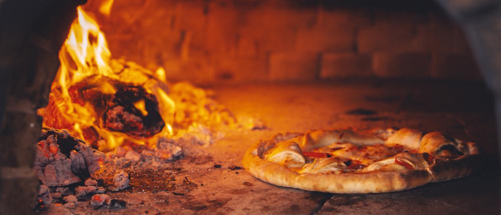 pizza wypiekana w piecu opalanym drewnem